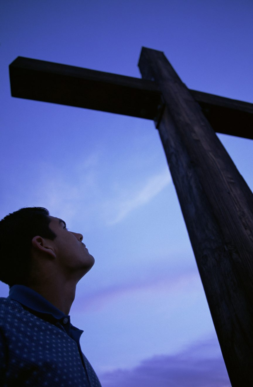 young man standing at foot of cross